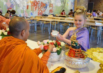 Fra songkran.høytiden - munken Phra Maha Khamsing får vann over hendene av ung deltaker