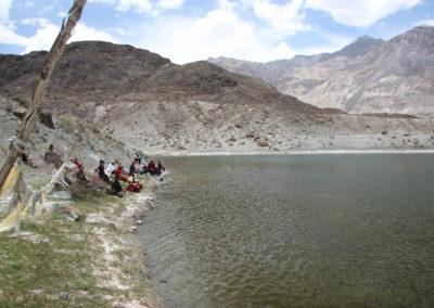 Pilegrimmer fra Karma Tashi Ling-sanghaen mediterer ved en hellig innsjø i Ladakh, Nord-India