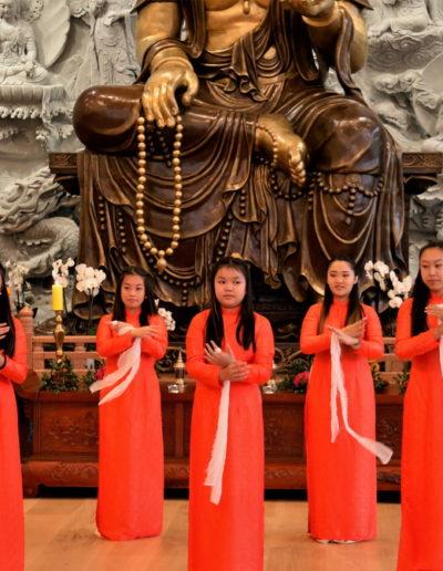Unge norsk-vietnamesiske kvinner opptrer foran statuen av Quan Te Am