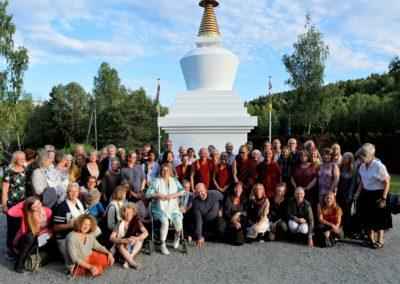Besøkende lærer Ringu Tulku Rinpoche med kursdeltagere foran stupaen på Karma Tashi Ling buddhistsenter